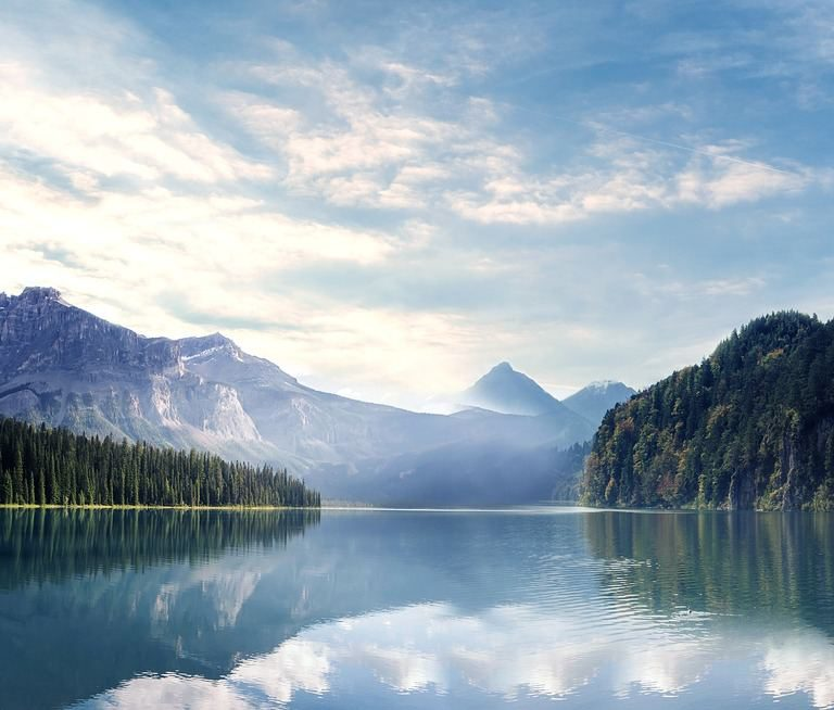 Scenic lake view with forests and mountains in the background