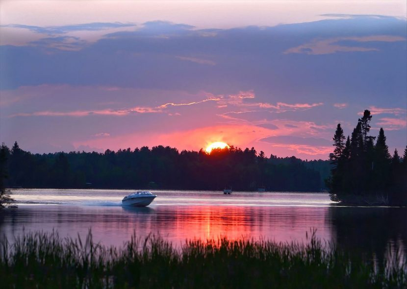 Scenic lake view with forests and a sunset in the background